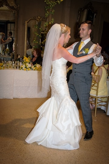 Bride in white wedding gown dancing with groom