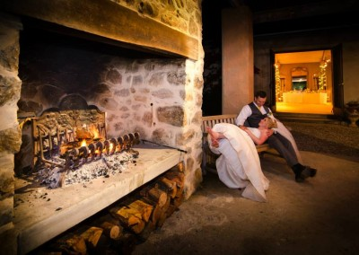 Wedding couple rest by the fireplace